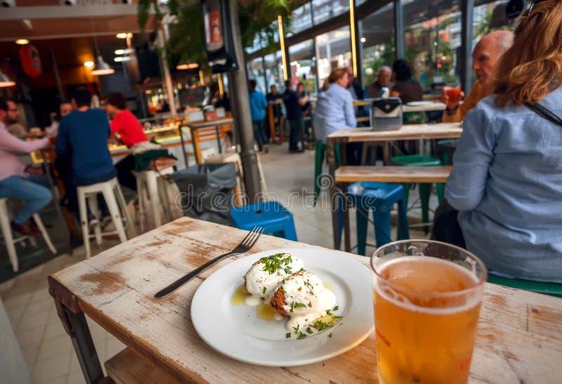 Tapas y vaso de cerveza en la tabla de mercado de la ciudad con la gente que se sienta alrededor de corte de la comida rápida imagen de archivo