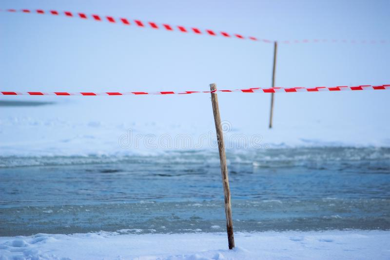 Tape fence on the winter river royalty free stock photography