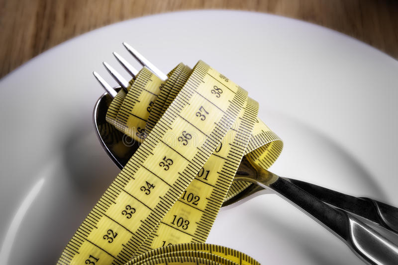 Tape measer with fork and spoon. Tape measure with fork and spoon on a plate royalty free stock image