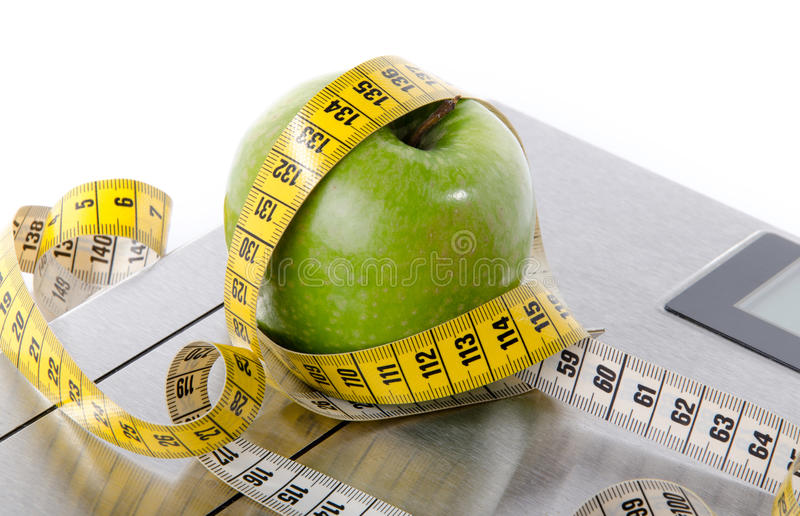 Tape measure around a green apple on a bathroom scales. Isolated on white royalty free stock image