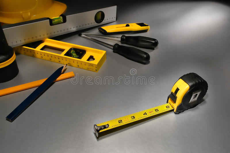 Tape Measure at Building Construction Work Site. Self retracting yellow tape measure tool in inch measurement on metal surface with assorted trade tools at stock photos