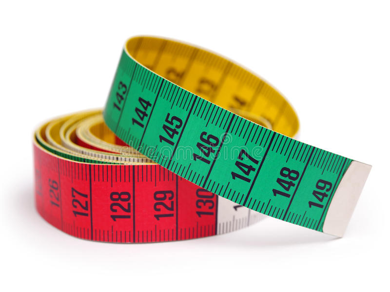 Tape measure. Closeup photo of a yellow, red, and green tape measure. Shallow depth of field stock images