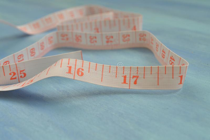 Tape measure half-rolled out. Measuring cm and inches. Tailoring tools. Pocket measure. Tape measure half-rolled out. Measuring cm and inches. Tailoring tools stock photo