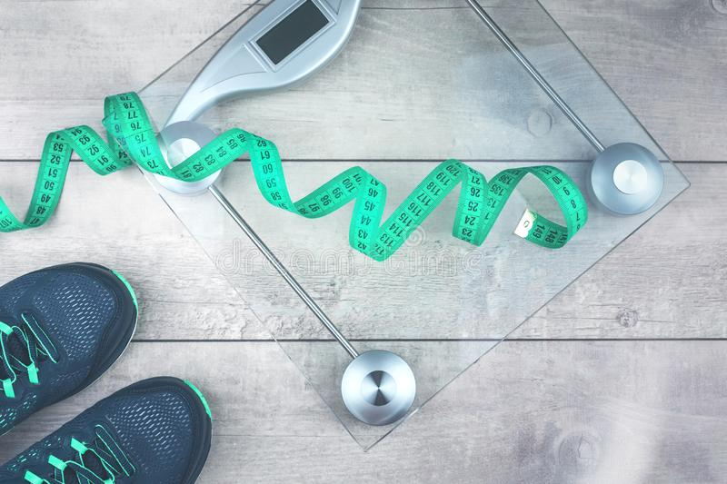 Tape measure, running shoes and weighing scales. Green measure tape, glass weighing scale, running shoes on a rustic surface. Weight management and healthy stock images