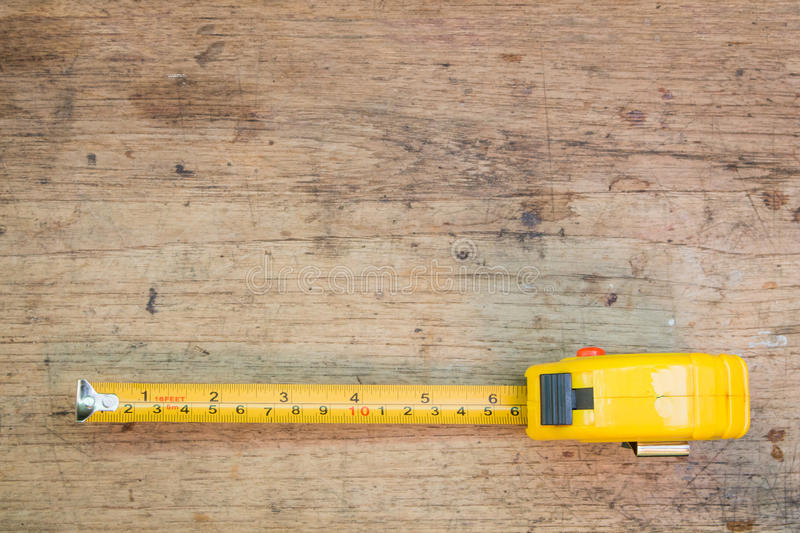 Tape measure,tape measure on the brown wooden background stock photos