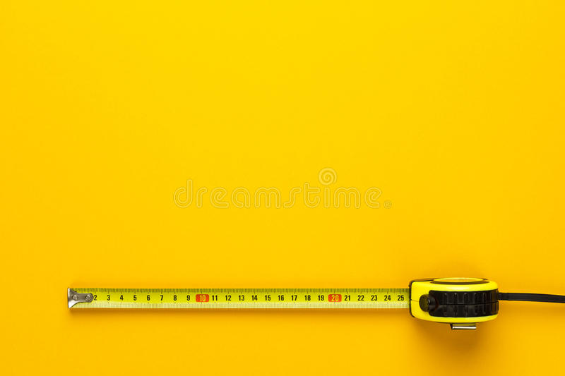 Tape measure on the yellow background royalty free stock photography