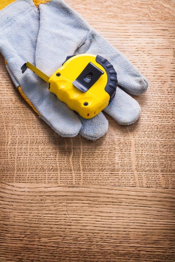 Tapeline и защитная работая перчатка на деревянном стоковая фотография rf