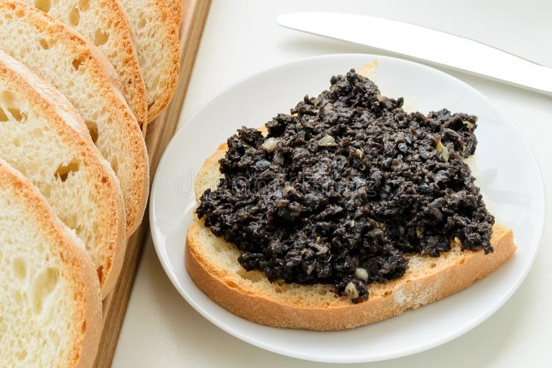 Tapenade sandwich on a sauser and sliced wheat bread on a wooden chopping board over white kitchen table. Homemade black olive stock photography
