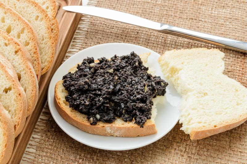 Tapenade sandwich on a sauser, table knife and sliced wheat bread on a burlap table napkin. Homemade black olive paste with royalty free stock photo