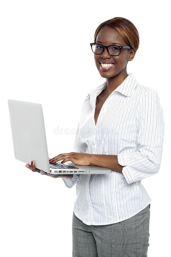 Taper exécutif femelle sur l'ordinateur portatif et fonctionner image stock