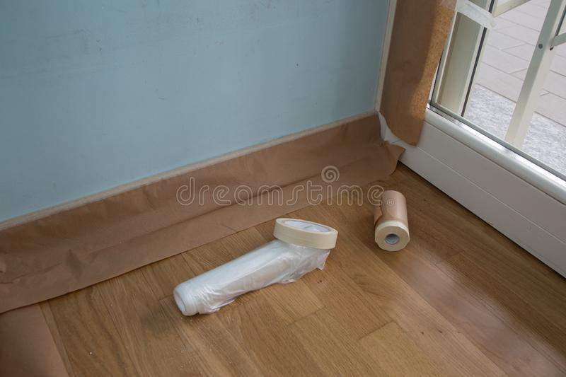 Tapes and Protective Sheeting applied to the Baseboard of the Walls for Painting.  royalty free stock photo