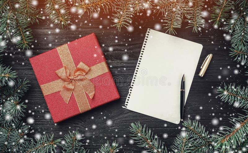 Tapet av vinterferier på svart träbakgrund Xmas-kort med ljus och snöeffekt claus bokstav santa arkivbild