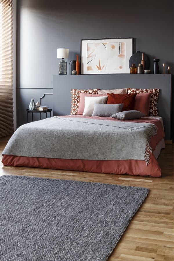 Tapete cinzento na frente de uma cama enorme com descansos e uma pintura imagens de stock
