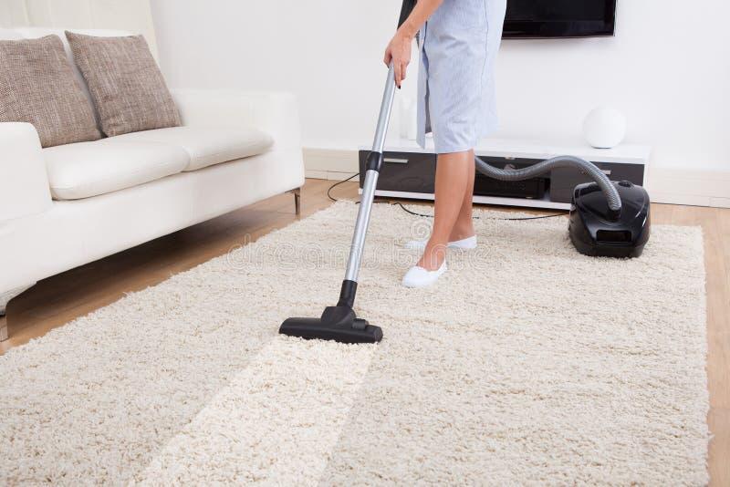 Tapete da limpeza da empregada doméstica com aspirador de p30 fotografia de stock royalty free