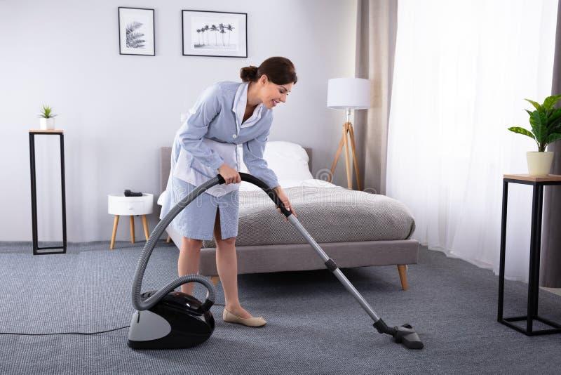 Tapete da limpeza da empregada com aspirador de p30 fotografia de stock