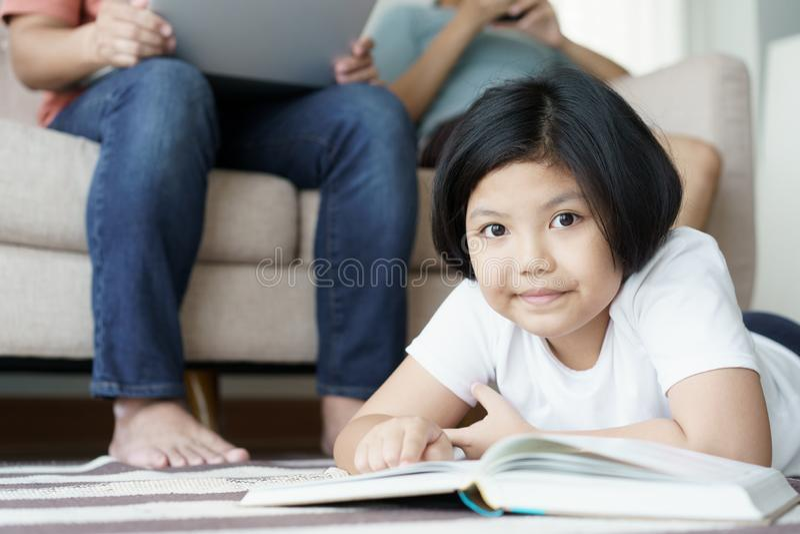 Tapete de jogo alegre da criança ascendente próxima na sala de visitas A família é mãe e filha do pai felizes junto na casa imagem de stock