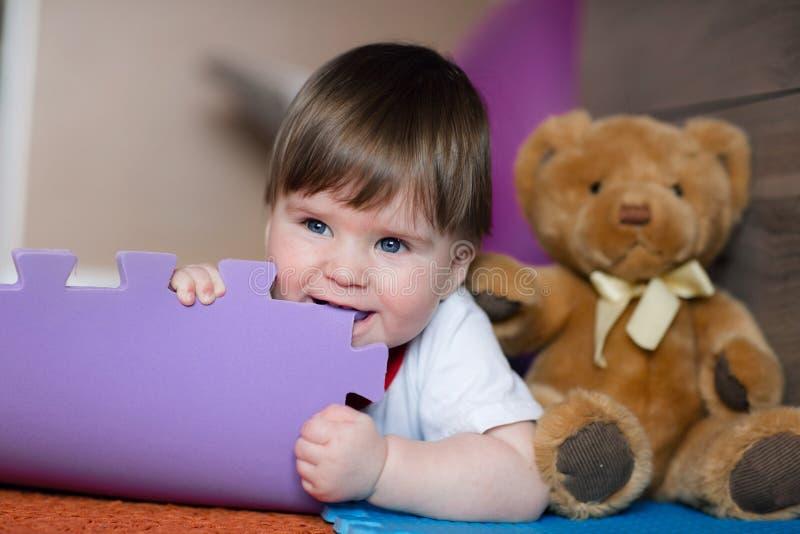 Tapete do ` s das crianças da mordida do bebê de um ano O bebê feliz encontra-se no assoalho na sala e no jogo do ` s das criança foto de stock