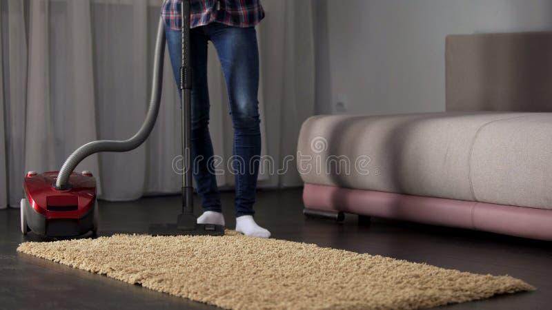 Tapete hoovering da empregada doméstica fêmea perto do sofá na sala de visitas, tarefas da casa, frescor imagem de stock royalty free