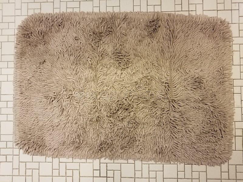 Tapete ou tapete do banheiro de Brown no assoalho de telha branco foto de stock