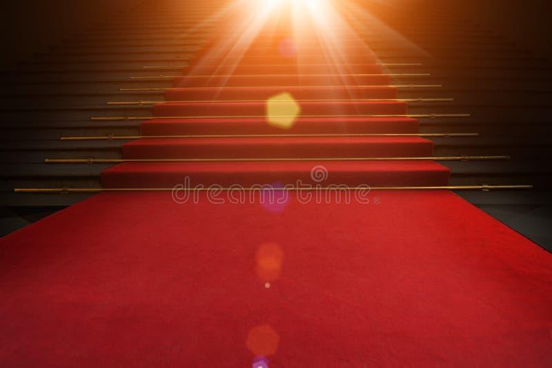 Tapete vermelho nas escadas em um fundo escuro O trajeto à glória, à vitória e ao sucesso imagem de stock