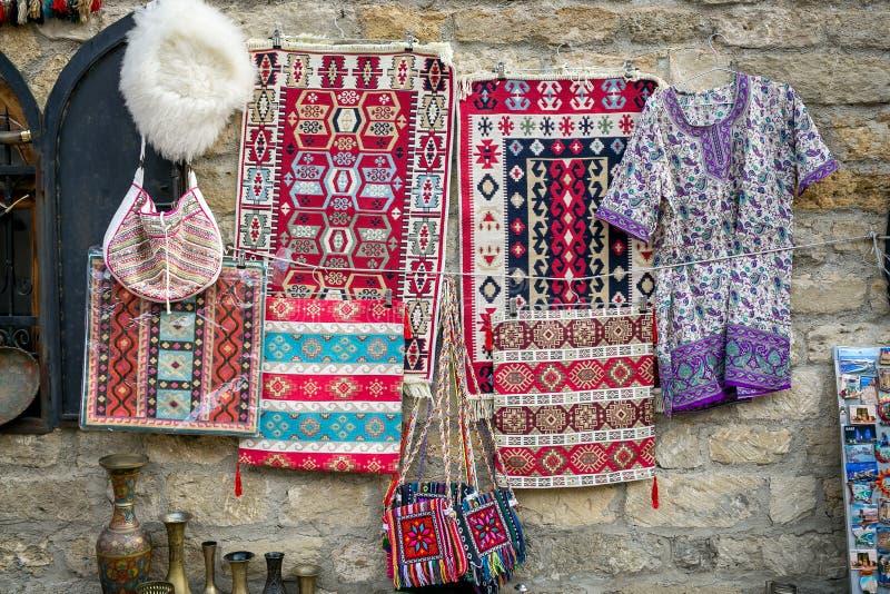 Tapetes com testes padrões feitos a mão azerbaijanos nacionais, chapéu branco feito de lãs feitos a mão dos carneiros, bolsas tec imagens de stock royalty free