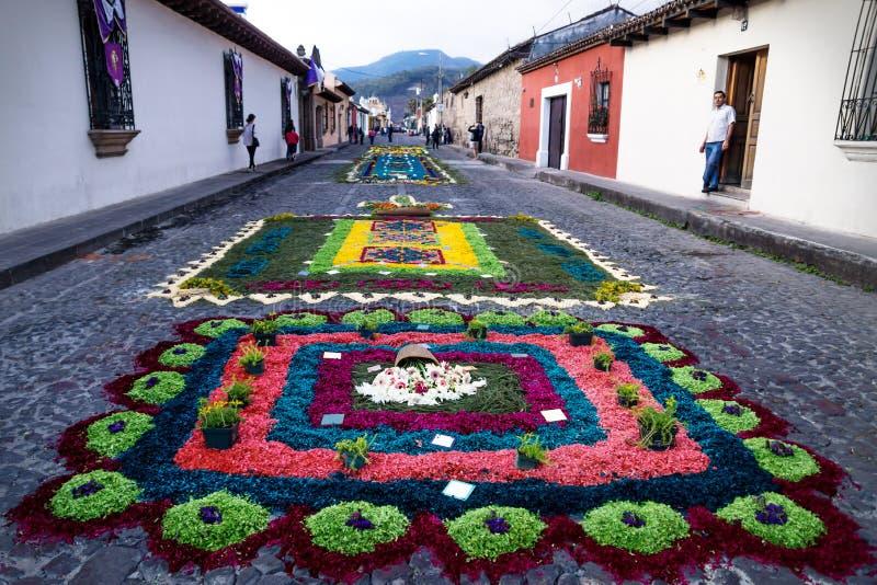 Tapetes da flor de Alfombre nas ruas cobbled ao longo das construções coloniais de Antígua, Guatemala fotos de stock royalty free
