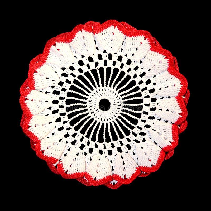 Tapetito blanco decorativo hecho a ganchillo aislado con la frontera roja en un fondo negro Tapetito volumétrico redondo imagen de archivo