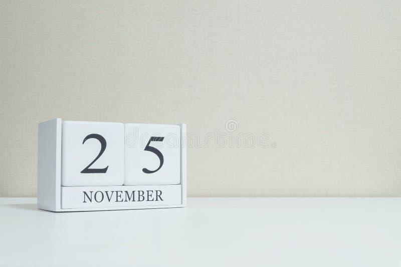 Tapetserar den vita träkalendern för closeupen med det svart25 november ordet på suddig vit wood skrivbord- och krämfärg i rum te royaltyfri fotografi
