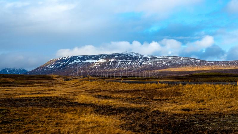 Tapetsikt till ängar och den snöig kullen i Island arkivbild