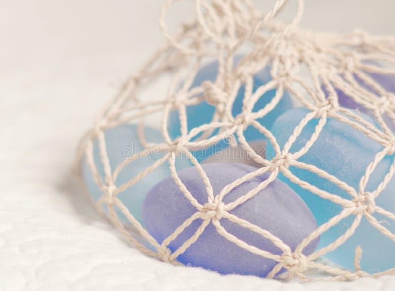 Tapezieren Sie in den Pastellfarben mit Glassteinen im Fischnetz lizenzfreie stockfotos
