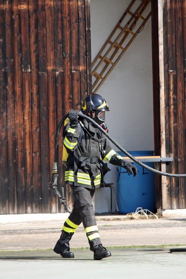 Tapfere Feuerwehrmänner mit Sauerstoffflaschefeuer während einer Übung gehalten lizenzfreie stockbilder
