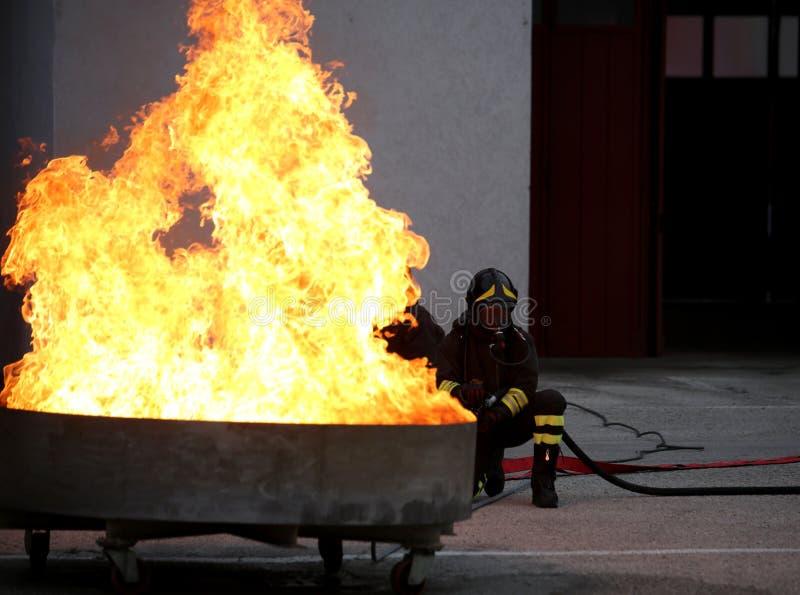 Tapfere Feuerwehrmänner während der Übung für das Feuer extinguishin stockfotografie