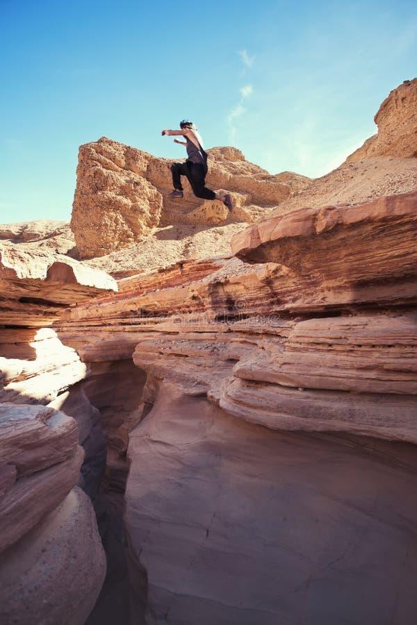 Tapferer Mann, der über die Klippe in der Schlucht springt lizenzfreies stockfoto