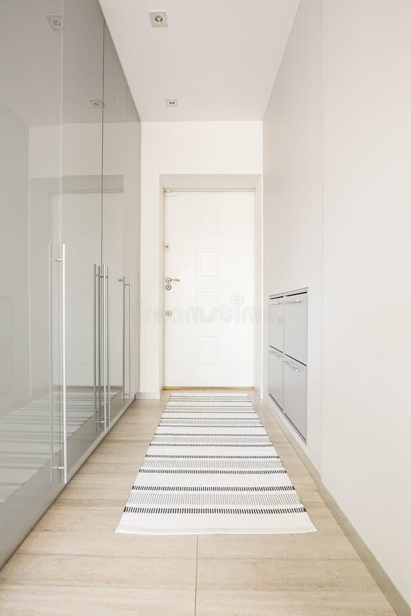 Tapijt op houten vloer in wit zaalbinnenland met deur Echte ph royalty-vrije stock foto