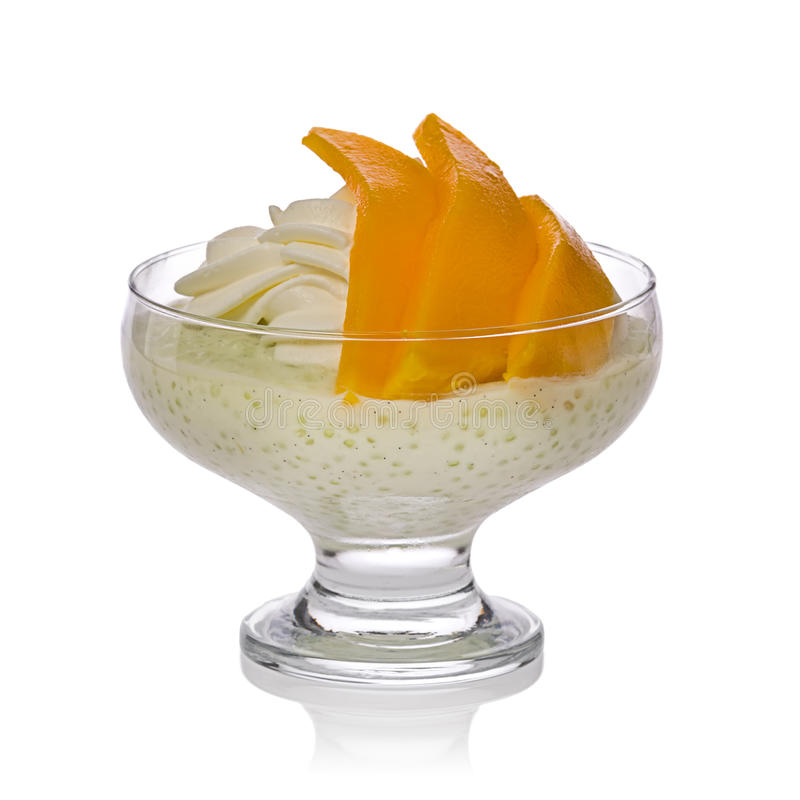Tapioca Pudding. With whipped cream and slices of mango in a glass bowl against a white background royalty free stock photography