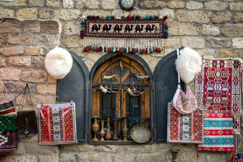Tapis avec les modèles faits main azerbaïdjanais nationaux, chapeau blanc fait de laine faite main de moutons, sacs à main tissés photographie stock libre de droits