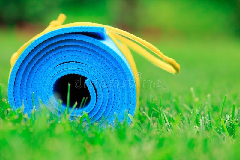 Tapis bleu de yoga sur l'herbe verte image stock