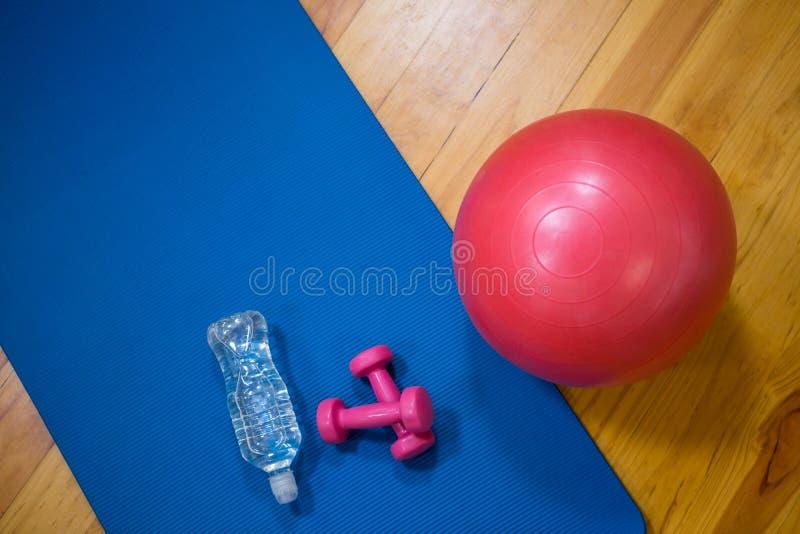 Tapis de boule, de bouteille d'eau, d'haltère et d'exercice de forme physique sur le plancher en bois photo libre de droits