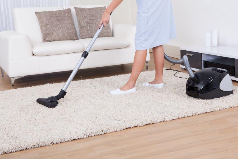 Tapis de nettoyage de domestique avec l'aspirateur photographie stock libre de droits