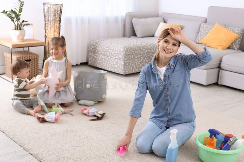 Tapis de nettoyage de femme au foyer tandis que ses enfants photo libre de droits