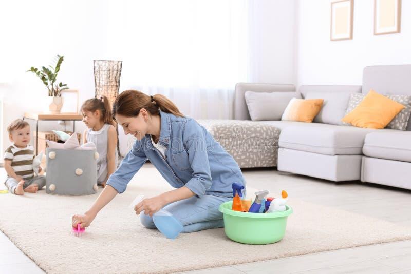 Tapis de nettoyage de femme au foyer tandis que ses enfants photos stock