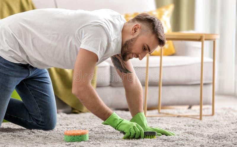 Tapis de nettoyage de jeune homme ? la maison image stock