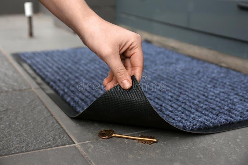 Tapis de porte de levage de la main de la femme pour indiquer la clé cachée dessous image stock