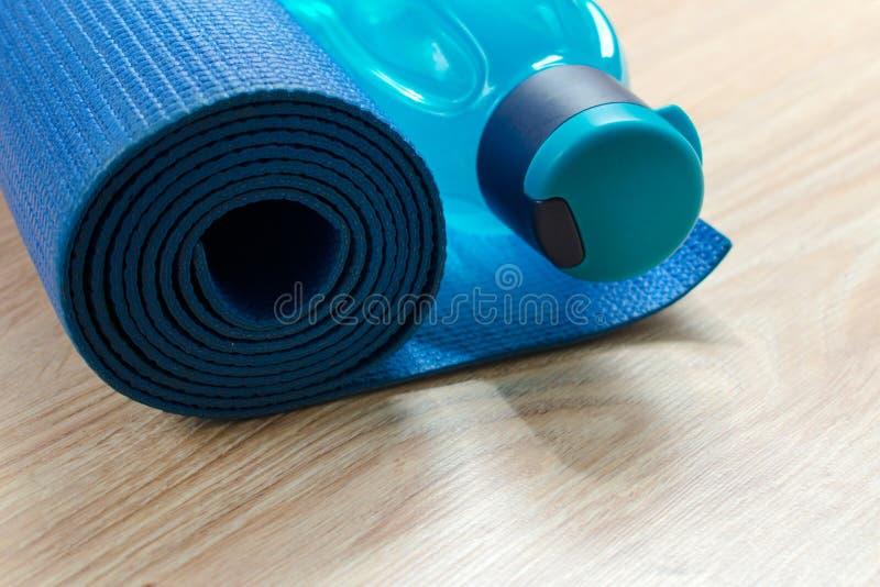 Tapis de yoga et une bouteille de l'eau, du concept de la formation et de récréation image stock