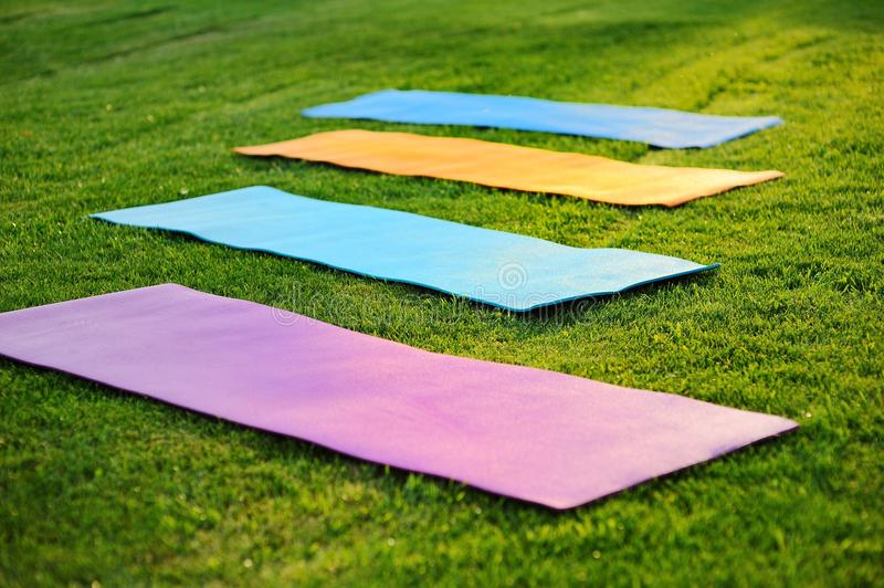 Tapis de yoga sur l'herbe verte photos stock