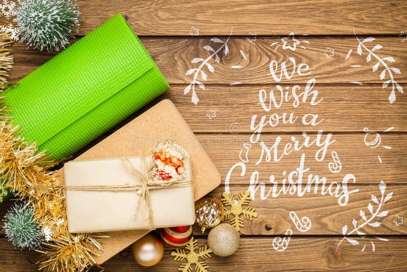 Tapis de yoga vert ou tapis de pilates avec bloc de yoga et boîte cadeau avec arbre de Noël ornement décoration sur bois pour Joy photographie stock libre de droits