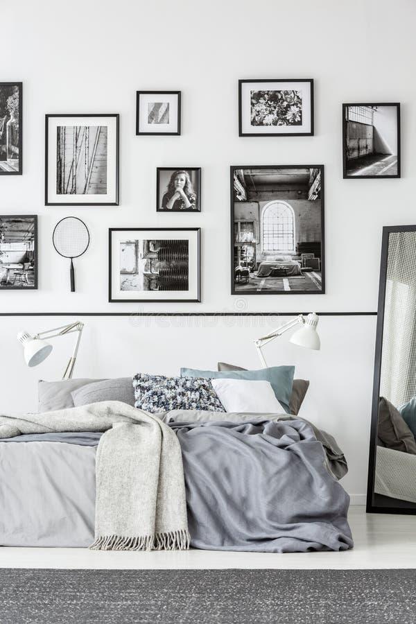 Tapis devant le lit et miroir dans l'intérieur blanc et noir de chambre à coucher avec la galerie Photo r?elle photo libre de droits