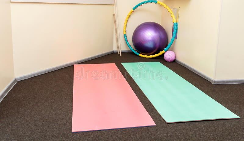 Tapis et boules gymnastiques dans une salle de réadaptation Gymnastique vide photos libres de droits