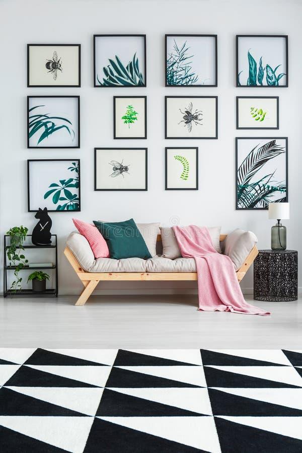 Tapis noir et blanc avec le modèle géométrique placé sur le plancher dans l'intérieur lumineux de salon avec le salon en bois ave images stock