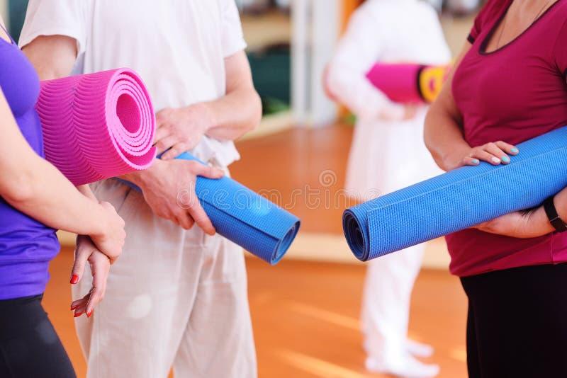 Tapis pour la forme physique ou le yoga dans les mains image libre de droits